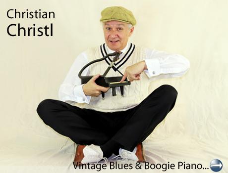 Ein Mann sitzt im Schneidersitze und zeigt auf ein kleines Modell eines Flügels (Klavier)